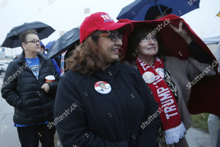 Donald Trump Supporters of Republican presidential candidate Donald Trump, Vinita Navani, center, and Lura Neel, right, both from Peoria, Ill., wait in a steady rain before a rally, in Bloomington, Ill
