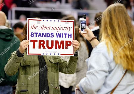 Elizabeth Hale places a campaign sign for Republican presidential candidate Donald Trump in front of her as her friend Hannah Read both of Searcy, Ark., takes her photo before a rally for Donald Trump, in Little Rock, Ark