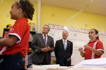 Jeb Bush, Asa Hutchinson Students Maya Gilbert, far left, and Pada Peral, far right, use American sign language as former Florida Gov. Jeb Bush, second from left and Republican candidate for Arkansas governor Asa Hutchinson, center right, watch at LISA Academy North in Sherwood, Ark