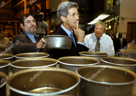 GIRARD KERRY JOHNSTON Democratic presidential candidate Sen. John Kerry, D-Mass., center, stands next to unfinished pots while touring the All-Clad cookware factory as Leo Girard, International President of the United Steelworkers of America, left, and All-Clad Chief Operating Officer Frank Johnston, right, look, in Canonsburg, Pa., . Kerry spoke about labor issues during the campaign stop