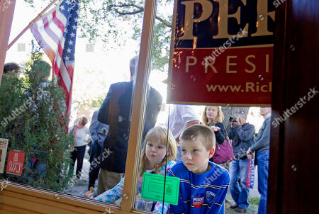 Rick Perry, Joseph Quinn, Bridget Quinn Joseph Quinn, 9, right, and his sister Bridget, 7, both of Summerville S.C., look inside a law firm as Republican presidential candidate, Texas Gov. Rick Perry met with supporters, in Summerville, S.C