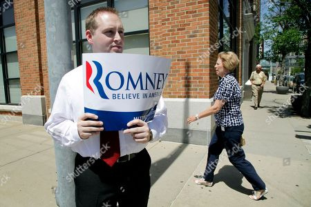 Stock Photo of Mitt Romney Patrick Finnegan, of Des Moines, Iowa, holds a campaign sign for Republican presidential candidate, former Massachusetts Gov. Mitt Romney outside a campaign stop, in Des Moines, Iowa