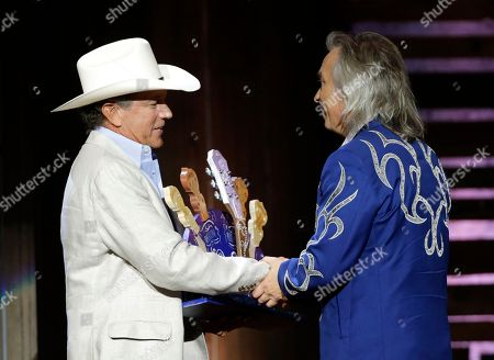 George Strait, left, presents Jim Lauderdale with the wagon master award