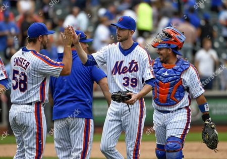 Josh Smoker, Jerry Blevins, Bartolo Colon, Rene Rivera New York Mets relief pitcher Josh Smoker (58), relief pitcher Jerry Blevins (39), starting pitcher Bartolo Colon (40) and catcher Rene Rivera celebrate their 3-2 2in over the Minnesota Twins in a baseball game, in New York