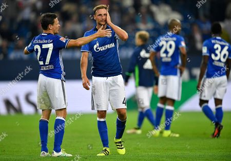 Schalke's Sascha Riether, left, and Schalke's Benedikt Hoewedes stand disappointed after losing the German Bundesliga soccer match between FC Schalke 04 and 1. FC Cologne in Gelsenkirchen, Germany, . Schalke was defeated by Cologne with 1-3