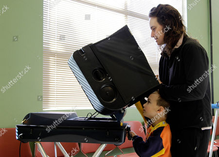 Stock Image of Aaron Sanders, 4, watches his mother, Rachel Sanders, vote at a polling place in Tacoma, Wash. Pierce County is the only county in the state of Washington with traditional voting locations still in use, as the rest of the state votes entirely by mail or by dropping completed ballots off at drop-box locations