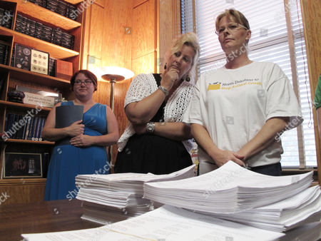 Karen Thunshelle, right, chairwoman of a North Dakota initiative campaign to make it a felony crime to commit acts of extreme cruelty against dogs, cats or horses, watches as workers in the North Dakota secretary of state's office process initiative petitions that were submitted to Secretary of State Al Jaeger's office in the North Dakota Capitol in Bismarck, N.D. Initiative supporters Alison Smith, center, of Bismarck, and Ellie Hayes, left, of Fargo, are standing with Thunshelle. Jaeger has about a month to review the petitions and decide whether they qualify for the November 2012 general election ballot. Supporters of the initiative said they gathered more than 25,000 signatures; only 13,500 valid names are needed