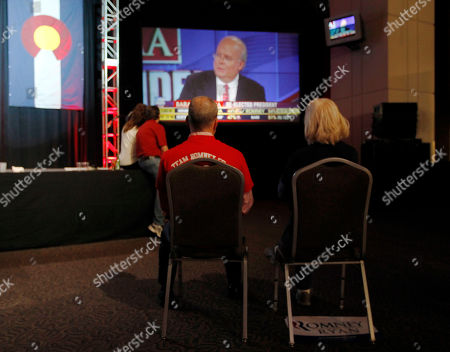 A couple sits on chairs in a near-empty room to watch Fox News commentator Karl Rove on a big-screen television during a Republican Party election night gathering in the club level of Sports Authority Field at Mile High in Denver on
