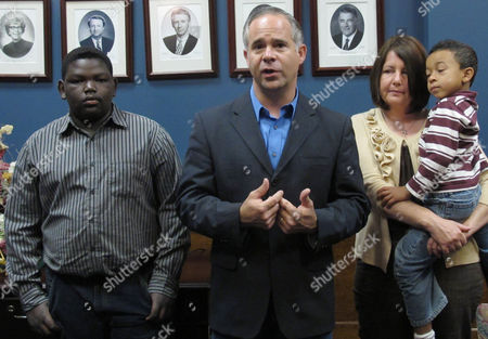 U.S. Rep. Tim Huelskamp, center, a Republican, answers questions from reporters after filing for re-election in the 1st Congressional District of central and western Kansas, at the Kansas secretary of state's office in Topeka, Kan. Flanking him are left, his son, Athan, and right, his wife, Angela, and another son, Alex