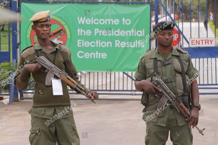 Armed police officers stand guard outside the presidential election results center following demonstrations by supporters of presidential candidate Hakainde Hichilema, a day after presidential elections in Lusaka, Zambia Wednesday, Jan, 21, 2015. Candidates vying to replace Zambia's late President Michael Sata have cast their ballots along with thousands of other voters in Tuesday's presidential election