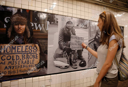 """Amanda Lachman Amanda Lachman of New York looks at portraits of the homeless by photographer Andres Serrano displayed on the walls of the West 4th Street subway station in New York, . Lachman said, """"They really caught my eye. They're really powerful images that show people what life can really be like, and that these people need help"""