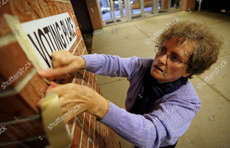 Poll worker Linda Blair hangs a sign before opening Precinct 39 up to allow voters to cast their ballots on Election Day, at the First Church of the Open Bible in Des Moines, Iowa