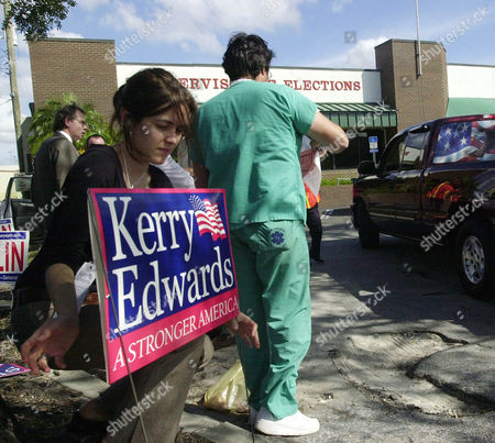 Stock Image of GILLIGAN CABRERA Kerry-Edwards campaign workers Anna Gilligan, left, puts up a Kerry-Edwards sign as Luis Cabrera, right, hands out sample ballots to motorists entering the Supervisor of Elections office for early voting in Orlando, Fla
