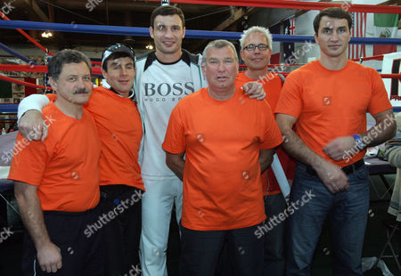 GYZHA Vitali Klitschko, third from left, poses for a group photo with his brother Wladimir, right, and team members wearing red-orange T-shirts in support of Ukranian presidential candidate Viktor Yuschenko, following a light workout and media availability at the La Brea Academy boxing gym in Los Angeles . From left are Wladimir Zolotarev, Roman Gyzha, Vitali Klitschko, his trainer Fritz Sdunek, mamanger Bernd Boente, and Wladimir Klitschko. Vitali Klitschko is preparing to meet Danny Williams for the heavyweight championship in a fight in Las Vegas on Dec. 11. He and his brother have also been outspoken in their protest of the disputed presidential election in Ukraine, their homeland
