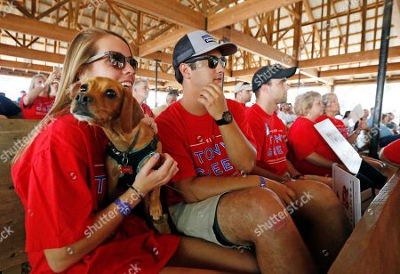 Corbin Stanford, Anna Kate Jackson, Tucker Corbin Stanford, second from right, and Anna Kate Jackson of Clinton, Miss., laugh as their dog, Tucker, growls during the candidate's speeches at the Neshoba County Fair in Philadelphia, Miss., . The fair is a traditional gathering place for politicians, area residents, business leaders, voters and families