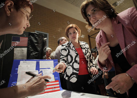 Christine Quinn, Kim Catullo City Council Speaker and New York City Democratic mayoral hopeful Christine Quinn, center, and her wife, Kim Catullo, right, sign in to vote in the primary election with an unidentified poll worker in New York, . Quinn led the polls for most of the year but has seen support disappear as her rivals linked her to the bitter debate to let Bloomberg run for a third term in 2009