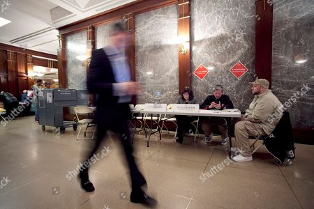 Brendan Reilly A resident of a luxury apartment building on Wall Street walks past a polling station in the lobby of his building, in New York. Voters in New York, Connecticut, Delaware, Rhode Island and Pennsylvania are voting in the presidential primaries Tuesday