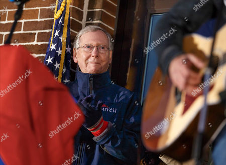 """Mitch McConnell Senate Minority Leader Mitch McConnell, R-Ky., listens as singer Jimmy Rose performs his ode to Kentucky, """"Coal Keeps the Lights On,"""" during a rally at the Scott County Courthouse Square in Georgetown Ky., Saturday night, . The results of the closely watched Kentucky contest will be crucial in the midterm election that could shift the balance of power in Congress"""