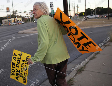 Stock Image of Carol Burton, an Obama campaign volunteer, searches for a location to place election day signs before polls open on Tuesday morning, in Austin, Texas. Burton has been a regular Democratic campaign volunteer since George McGovern ran for president in 1972