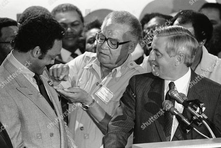 Detroit Mayor Coleman Young, center, pins a Mondale-Ferraro button on the Rev. Jesse Jackson, left, as Democratic presidential nominee, Walter Mondale at a press conference following at night, in St. Paul, meeting between Mondale, Jackson and other black leaders Mondale hopes will help his election potential in November. Jackson lent his ?deep and intense? support to Mondale