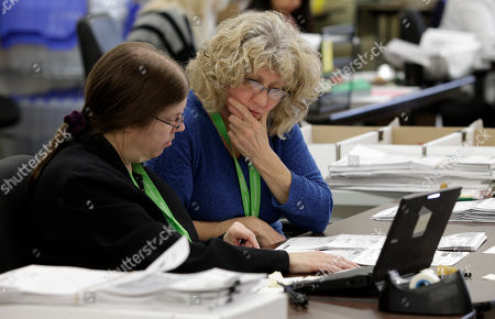 Debi Hertel, left, and Shaw Dixon, right, review ballots at King County's ballot processing facility, in Renton, Wash. Election officials estimate that hundreds of thousands of votes were left to count on Wednesday, including those in the very close Governor's race between Democrat Jay Inslee and Republican Rob McKenna