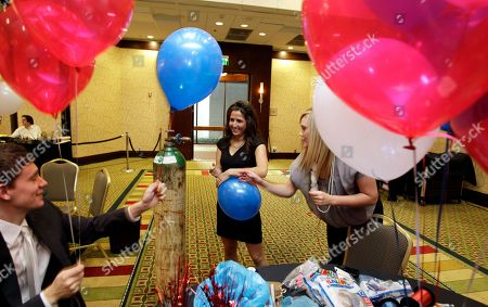 Dillon Heist, left, Kathryn Gunter, center, and Caitlin Shannon, right, interns with the Washington state Republican Party, blow up balloons as they help decorate the hotel ballroom where Republican Dino Rossi will talk to supporters, in Bellevue, Wash. Rossi is challenging Sen. Patty Murray, D-Wash., for her seat in the Senate