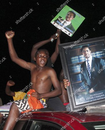 Stock Photo of Supporters of the Patriotic Front hold portraits of their presidential candidate Edgar Lungu and celebrate after an announcement that Lungu won the presidential elections in Lusaka, Zambia, . Lungu narrowly defeated his rival Hakainde Hichilema in the contest to succeed Michael Sata, who died in office in October at 77