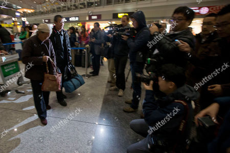 Wang Jinxiang, left, the mother of blind Chinese dissident Chen Guangcheng, and his brother Chen Guangfu, second from left, walk near journalists as they prepare to take a flight to New York, at the capital airport in Beijing, China, . The mother and brother will visit Chen Guangcheng, the prominent human rights activist who has lived in New York since soon after escaping house arrest in China in dramatic fashion in April last year with his wife and two children. Chen dodged a security cordon around his home in east China's Shandong province and sought refuge in the U.S. Embassy in Beijing. Then Secretary of State Hillary Clinton prevailed on Chinese officials to allow him to leave for the U.S