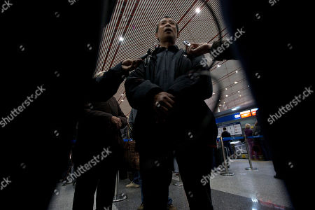 Chen Guangfu, the brother of blind Chinese dissident Chen Guangcheng, talks to journalists as he prepares to bring his mother to New York, at the capital airport in Beijing, China, . The mother and brother will visit Chen Guangcheng, the prominent human rights activist who has lived in New York since soon after escaping house arrest in China in dramatic fashion in April last year with his wife and two children. Chen dodged a security cordon around his home in east China's Shandong province and sought refuge in the U.S. Embassy in Beijing. Then Secretary of State Hillary Clinton prevailed on Chinese officials to allow him to leave for the U.S