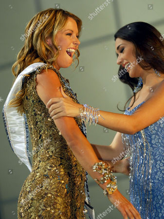 Miss Universe 2004 Jennifer Hawkins, of Australia, left, receives her sash from former Miss Universe Amelia Vega in Quito, Ecuador