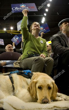 Stock Photo of Deborah Allen Barack Obama supporter Deborah Allen holds up her sign while her companion labrador Hartford rests on the floor at the beginning of the Ada County Democratic Caucus inside the CenturyLink Arena downtown Boise, Idaho. Several thousand people jammed into the indoor arena while hundreds were turned away because no more room was available inside. Democrats head to caucuses in each of Idaho's 44 counties, and organizers expect record turnout for the contest between Hillary Clinton and Bernie Sanders