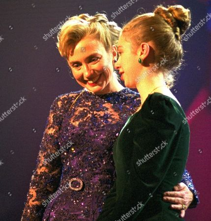 Hillary Rodham Clinton, Chelsea Clinton First lady Hillary Clinton putting her arm around her daughter Chelsea as they attend the MTV Ball at the Washington Convention Center. Mrs. Clinton's gown was designed by New Yorker Sarah Phillips, who estimated its value at $50,000