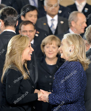 US Secretary of State Hillary Clinton, right, meets Spain's foreign minister Trinidad Jimenez Garcia-Herrera at the international Afghanistan conference in Bonn, Germany, . German chancellor Angela Merkel watches from the background. A decade after the first Afghanistan conference the international community discusses the future of its engagement in Afghanistan
