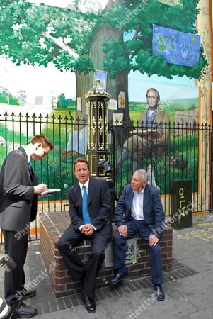 David Cameron and Bromley by election Conservative candidate Bob Neill, sitting in front of a mural of Charles Darwin.