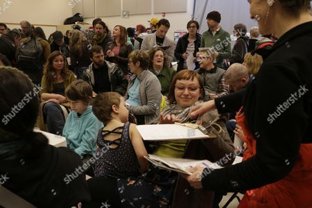 Jessica Olson, seated, signs a petition offered up by another Democratic caucus attendee,, in Olympia, Wash. Olson attended the caucuses with her family to support Bernie Sanders