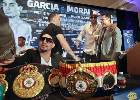 Danny Garcia, left foreground, super lightweight world boxing champion, is surrounded with his championship belts as Oscar De La Hoya, far right, president of Golden Boy Promotions, greets Brooklyn boxers Paulie Malignaggi, second from right, welterweight world champion, and Boyd Melson, a junior middleweight prospect, before a news conference, in Brooklyn, N.Y. Golden Boy Promotions will presents the first boxing event at Brooklyn's new Barclays Center arena, headlining Garcia and Erik Morales in a championship match on Saturday, October 20