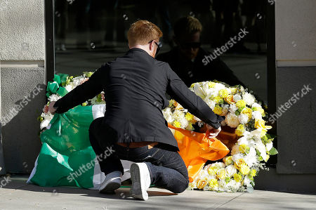 Neil Sands of the Irish Network Bay Area places a flag of Ireland over wreaths at the Library Gardens apartment complex in Berkeley, Calif. On, Ireland President Michael Higgins is planning to visit Berkeley to plant a tree in memory of the five Irish college students and one Irish-American who were killed when a balcony snapped off a downtown apartment building