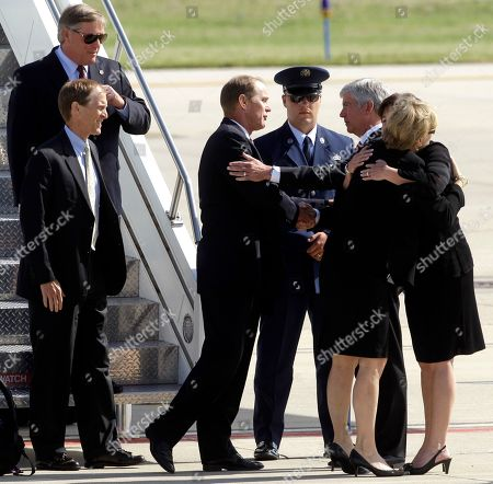 Susan Ford Bales, right, hugs Sue Snyder as Michigan Gov. Rick Snyder, third from right, shakes hands with Michael Ford as Steve Ford, bottom at left, and Jack Ford, top at left, exit the plane carrying the caskey of former first lady Betty Ford at Gerald R. Ford International Airport in Cascade Township, Mich., Wednesday, July, 13, 2011. Ford will be buried in Grand Rapids, Mich., on Thursday next to her husband, former President Gerald R. Ford