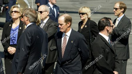 From left, Susan Ford Bales, Jack Ford, Michael Ford, center, and Steve Ford, far right, watch as a military honor guard transfers the casket of their mother, former first lady Betty Ford, to a U.S. Air Force C-32 for a flight to Grand Rapids, Mich., at Palm Springs International Airport in Palm Springs, Calif., . Ford will be buried in Michigan on Thursday next to her husband former President Gerald R. Ford
