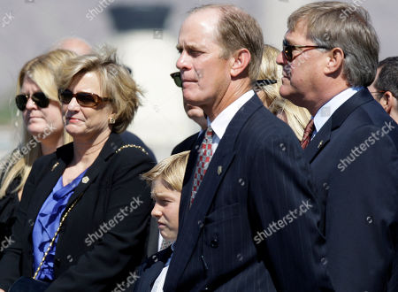 From second left, Susan Ford Bales, Michael Ford and Jack Ford watch as a military honor guard transfers the casket of their mother, former first lady Betty Ford, to a U.S. Air Force C-32 for a flight to Grand Rapids, Mich., at Palm Springs International Airport in Palm Springs, Calif., . Ford will be buried in Michigan on Thursday next to her husband former President Gerald R. Ford