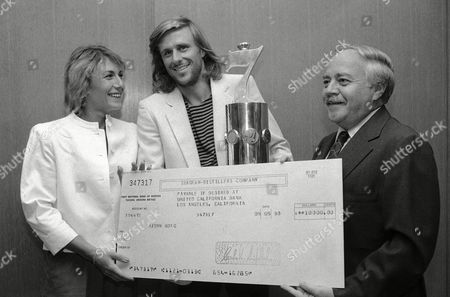 Bjorn Borg, Mariana Simionescu Borg, Walter Haimann Bjorn Borg, center, and his wife Mariana Simionescu smile, as Walter M. Haimann, president of Seagram Distillers Co., presents them with a large check, and the Seagram trophy in New York. Both the $10,000 check and trophy went to Borg as the winner of the firm's Seven Crowns of Sports competition, a computer-based evaluation of every game, set, and match played over the year