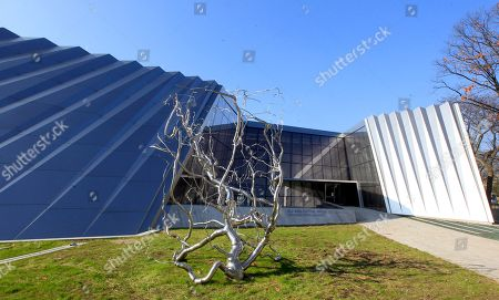 """Stock Photo of In a photo a stainless steel sculpture titled """"Containment I"""" by Roxy Paine is displayed outside an entrance to the Eli and Edythe Broad Art Museum on the campus of Michigan State University in East Lansing, Mich. The museum features Zaha Hadid's signature look: a facade of pleated stainless steel and glass, which distinguishes it from the traditional brick Collegiate Gothic buildings that surround it on Michigan State's north campus"""
