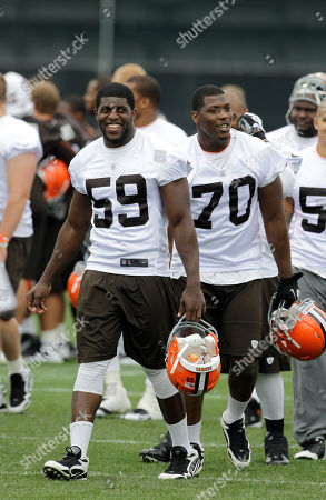 Emmanuel Acho, Brian Sanford Cleveland Browns rookie linebacker Emmanuel Acho (59) walks off the field with lineman Brian Sanford (70) following an off-season practice at the NFL football team's headquarters in Berea, Ohio