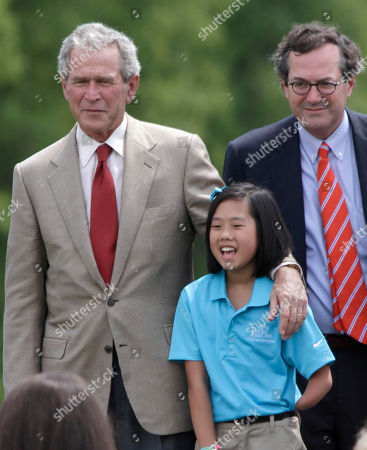 George W Bush, Warren Stephens Rebekah Walker, 11, poses with former President George W. Bush, left, as Warren Stephens looks on at The First Tee of Little Rock Jack Stephens Youth Golf Academy in Little Rock, Ark