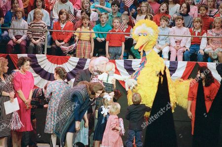 First lady Barbara Bush stands behind children, Big Bird and actor Wilford Brimley as Marilyn Quayle, wife of the vice president, looks to her right, during an Inaugural Celebration of the American Presidency for Young People in Washington