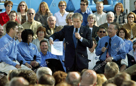 BUSH President Bush holds up his notes after dropping them on the floor while addressing a group of citizens on the economy, in Bakersfield, Calif., . Also on the stage are employees from Rain for Rent, an irrigation system business, Ismael Diaz, left, Theresa Avila, second from left, and the companys president John Lake