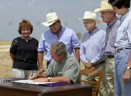 "COMBS President Bush, seated, signs a $5.5 billion agricultural spending bill, on his property near Crawford, Texas. Looking, from left, are ranchers and farmers: Reba ""Jean"" Davis, Joe Aguilar, John Dudley, Pierce Miller and Texas Agriculture Commissioner Susan Combs"
