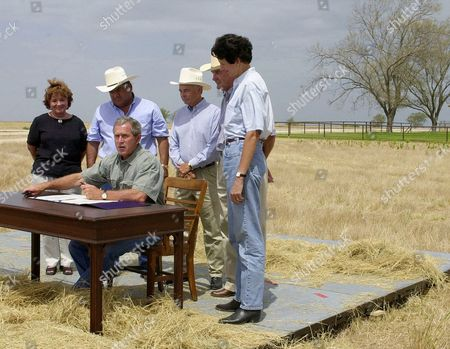 "Stock Photo of COMBS President Bush, seated, makes comments during a farm bill signing ceremony on his property, near Crawford, Texas. Looking, from left, are ranchers and farmers: Reba ""Jean"" Davis, Joe Aguilar, John Dudley, Pierce Miller and Texas Agriculture Commissioner Susan Combs"