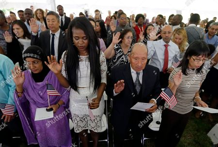 Rodolfo David Miranda, right center, of Peru, and Samira Dauda, left center, of Niger take the Oath of Allegiance at a naturalization ceremony at the Benjamin Harrison Presidential Site in Indianapolis, . Judge Sarah Evans Barker naturalized 101 new citizens at the ceremony