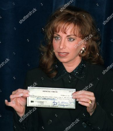 JONES HIRSHFELD Paula Jones holds up a check for $1 million given to her by New York real estate tycoon Abe Hirschfeld during a news conference at a Washington Hotel . The money would become part of an overall settlement of Jones's sexual harassment suit against President Clinton, though a spokeswoman for the former Arkansas state worker said there was no deal yet